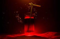 Glas des roten alkoholischen Cocktails auf dunklem Hintergrund mit Rauche und Hintergrundbeleuchtung Feuer heißes coctail Vereink Stockbilder