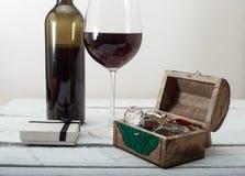 Glas des Rotweins, des Kastens mit Diamanten und des Geschenks auf weißem hölzernem Hintergrund, Feierliebe Lizenzfreies Stockbild