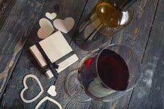 Glas des Rotweins und des Geschenks auf einem hölzernen Hintergrund Lizenzfreie Stockfotografie