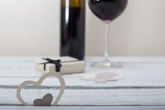 Glas des Rotweins und des Geschenks auf einem hölzernen Hintergrund Stockbilder