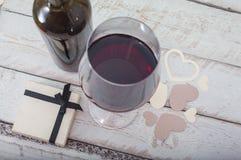 Glas des Rotweins und des Geschenks auf einem hölzernen Hintergrund Lizenzfreie Stockbilder
