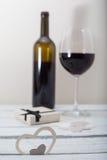Glas des Rotweins und des Geschenks auf weißem hölzernem Hintergrund, Feierliebe Lizenzfreies Stockbild