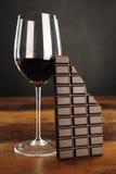 Glas des Rotweins und des Schokoriegels stockfotos