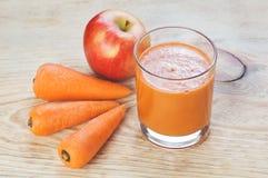 Glas des selbst gemachten Safts, des Apfels und der Karotte an Stockfoto