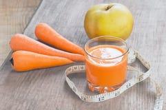 Glas des selbst gemachten Safts, des Apfels und der Karotte auf hölzernem Brett Stockfotografie