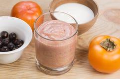 Glas des Smoothie der Persimone und der schwarzen Johannisbeere mit Milch, verziert durch Bestandteile auf rustikalem hölzernem B Lizenzfreies Stockfoto