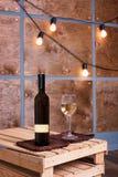 Glas des Weißweins und der Flasche im modernen Dachbodeninnenraum mit heller Girlande auf hölzerner Wand Stockbilder