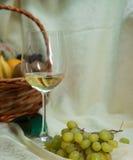 Glas des Weißweins und des Obstkorbes Lizenzfreie Stockfotografie