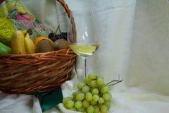 Glas des Weißweins und des Obstkorbes Stockbilder