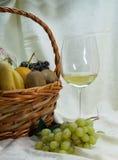 Glas des Weißweins und des Obstkorbes Stockfoto