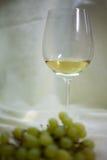 Glas des Weißweins und des Obstkorbes Stockfotos