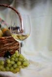 Glas des Weißweins und des Obstkorbes Lizenzfreies Stockbild