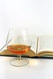 Glas des Weinbrands und des Buches Stockbilder