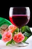 Glas des Weins, der Blume und der Uhr Stockfotografie