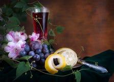 Glas des Weins, der rosa Blumen, der Trauben und der Zitrone Stockbilder