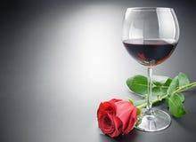 Glas des Weins und der rosafarbenen Blume Lizenzfreies Stockbild