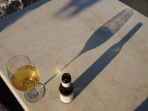 Glas des Weins und der Weinflasche auf einer Tabelle, angesehen von oben, mit langen Schatten Lizenzfreies Stockfoto