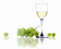 Glas des Weißweins und der Niederlassung der Trauben Stockfotografie