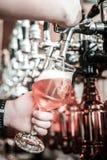 Glas die pale ale klaar in de handen van barkeeper worden royalty-vrije stock foto