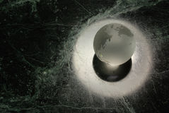 A glass earth. A glas earth orb with a halo on a 'universe' background Stock Photography