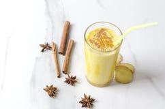 Glas eigengemaakte kurkuma latte met kaneel, steranijsplant en stukken van gember, het drinken stro royalty-vrije stock afbeelding