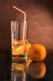 Glas eines Getränks mit einer Tangerine Stockfoto
