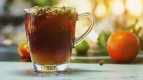 Glas Eistee mit Ñ- hrysanthemums und Orange, Eiswürfel auf dunklem Holztisch stock video footage