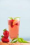 Glas Erdbeerlimonade mit Stücken der Erdbeere, der Zitrone und der frischen Minze stockfoto