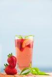 Glas Erdbeerlimonade mit Stücken der Erdbeere, der Zitrone und der frischen Minze Lizenzfreies Stockfoto