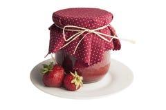 Glas Erdbeermarmelade auf weißer Platte Stockfotografie