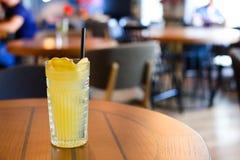Glas- exponeringsglas står på tabellen med att dricka sugrör, som vart pouen arkivfoton