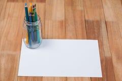 Glas farbige Bleistifte hielt auf Weißbuch Stockbild