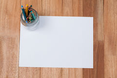 Glas farbige Bleistifte hielt auf Weißbuch Lizenzfreie Stockfotografie