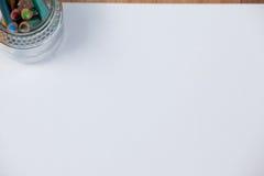 Glas farbige Bleistifte hielt auf Weißbuch Stockbilder