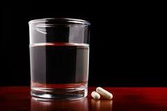Glas freies Wasser und Pillen auf Dunkelheit Lizenzfreies Stockfoto