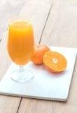 Glas frischer Orangensaft mit halb Orange Stockfotografie