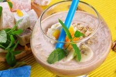 Glas Fruchtgetränk und türkische Freude Bananenmilchshake und türkische Freude Auf einem gelben Hintergrund Smoothies des strenge lizenzfreies stockbild