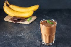 Glas fruit banaan-chocolade smoothie met muntbladeren en ingridients op de donkere achtergrond Gezond, vegetarisch, veganistdieet Royalty-vrije Stock Afbeeldingen