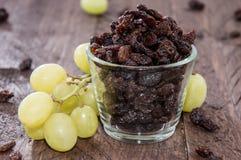 Glas gefüllt mit Rosinen (und Trauben) Stockfoto