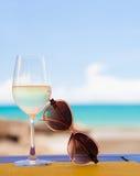 Glas gekoelde witte wijn en zonnebril op lijst dichtbij het strand Stock Fotografie