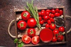 Glas geschmackvoller organischer Tomatensaft und frische Tomaten und Kräuter auf hölzernem Behälter in der rustikalen Art Lizenzfreies Stockbild