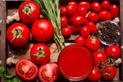 Glas geschmackvoller organischer Tomatensaft und frische Tomaten und Kräuter auf hölzernem Behälter in der rustikalen Art Stockbilder