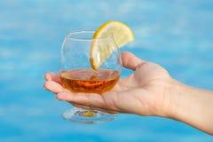 Glas geurige cognac met een plak van citroen in een vrouwen` s hand op een blauwe achtergrond stock foto