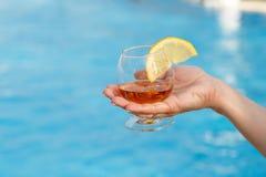 Glas geurige cognac met een plak van citroen in een vrouwen` s hand tegen een achtergrond van blauw poolwater stock fotografie