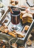 Glas Glühwein mit Lebkuchenplätzchen, Nüsse, Gewürze lizenzfreie stockfotografie