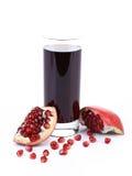 Glas Granatapfelsaft mit geschnittenen Früchten Lizenzfreie Stockfotografie