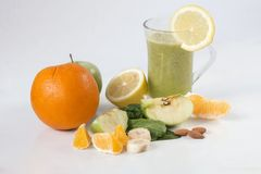 Green smothie with fresh fruits. Glas of healthy smoothie with spinach leaf and fruits including orange, banana, almond, lemon and green apple stock photography