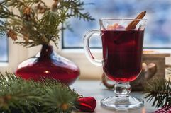 Glas heißer Glühwein auf Holztisch mit Kerzen-, Orangen-, Zimt- und Weihnachtsbaum Stockfotografie