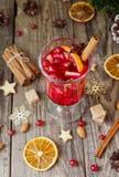Glas heißer Glühwein für das neue Jahr mit Bestandteilen für das Kochen, die Nüsse und die Weihnachtsdekorationen stockfoto