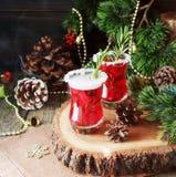 Glas heißer Glühwein für das neue Jahr mit Bestandteilen für das Kochen, die Nüsse und die Weihnachtsdekorationen stockbild